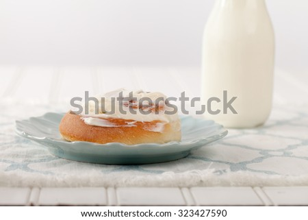 Freshly baked homemade cinnamon roll with cream cheese buttercream frosting and an antique bottle of milk side view - stock photo
