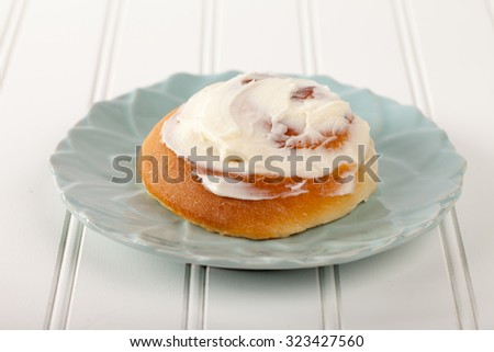Freshly baked homemade cinnamon roll with cream cheese buttercream frosting on a white board - stock photo