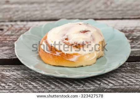 Freshly baked homemade cinnamon roll with cream cheese buttercream frosting on an old barn wood table - stock photo