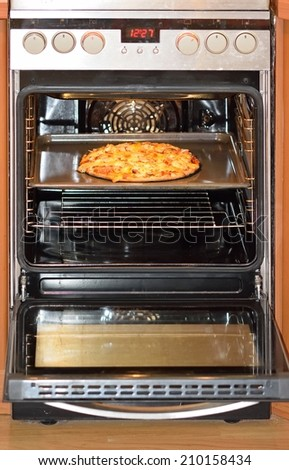 Freshly baked homemade pizza in the electric oven - stock photo