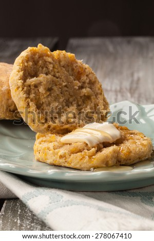 freshly baked homemade pumpkin biscuits opened up with honey and butter - stock photo