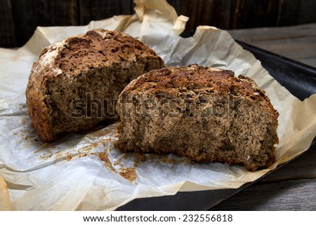 Freshly baked homemade rye bread on a baker's parchment - stock photo