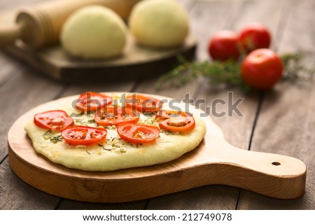 Freshly baked homemade yeast-dough flatbread topped with tomato slices, garlic and thyme leaves served on wooden board (Selective Focus, Focus on the front of the first tomato slices)   - stock photo