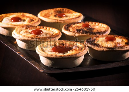Freshly baked meat pies with sauce and high contrast lighting. - stock photo