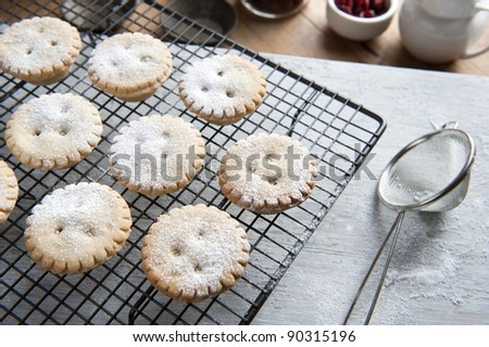Freshly Baked Mince Pies on a Cooling Rack and Been Sprinkled With Icing Sugar - stock photo