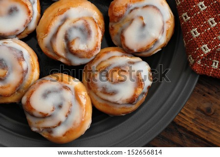 Freshly baked mini cinnamon rolls on plate with handwoven napkin and wood background.   - stock photo