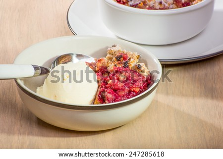 Freshly baked mixed berry crumble in a small dish, served with vanilla ice cream. - stock photo