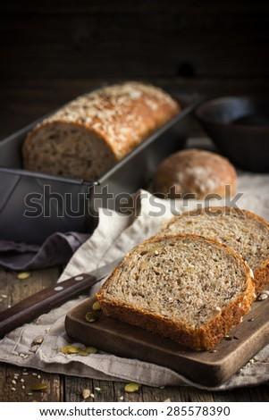 freshly baked  multigrain bread on rustic background - stock photo