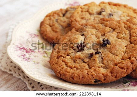 Freshly baked oatmeal raisin cookies on antique plate with distressed wood as background.  Macro with shallow dof. - stock photo
