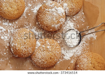 Freshly baked old-fashioned sugar cookies being dusted with powdered sugar.  Composition includes stainless steel powdered sugar duster and parchment paper over wood background.  Top view.