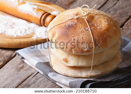 freshly baked pita bread on a wooden table close-up. rolling pin and flour in the background. horizontal  - stock photo