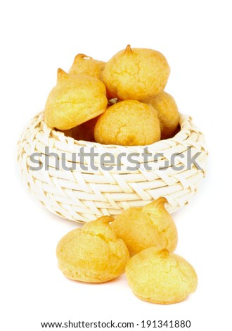 Freshly Baked Profiteroles in Wicker Bowl isolated on white background