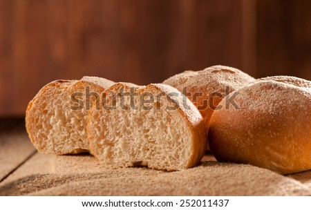 Freshly baked sliced buns on wooden board