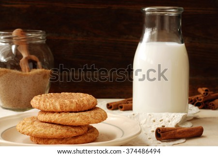 Freshly baked snickerdoodle cookies in rustic setting with old-fashioned milk bottle, cinnamon sticks, and antique lace napkin against a wood background.  Closeup with soft, natural side lighting.