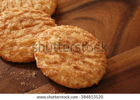 Freshly baked snickerdoodle cookies on wooden serving tray with distinctive wood grain pattern.  Closeup with shallow dof. - stock photo