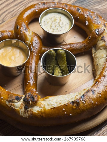 Freshly baked soft pretzel with coarse salt on wooden cutting board, served with whole grain mustard, cornichon pickles and honey mustard.  Closeup. - stock photo