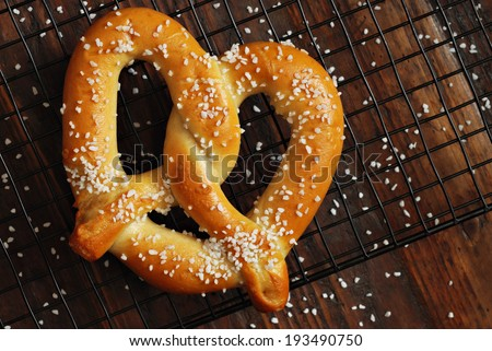 Freshly baked soft pretzel with generous sprinkling of coarse salt on wire cooling rack over rustic dark wood.  Closeup from above. - stock photo