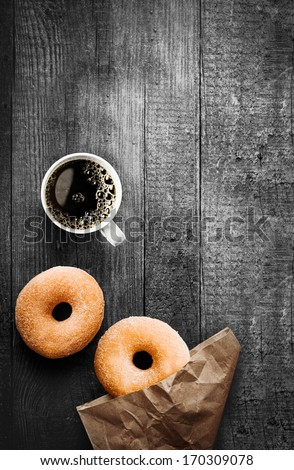 Freshly baked sugared ring doughnuts with a mug of full roast filter coffee and brown paper packaging on a grungy old wooden table in a rustic kitchen for breakfast snack - stock photo