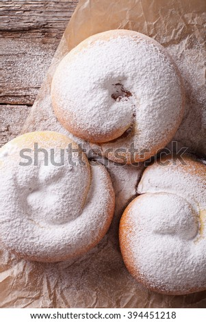 freshly baked sweet rolls ensaimadas with powdered sugar close-up on the table. vertical view from above - stock photo