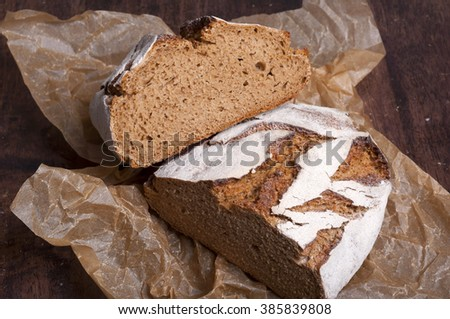 Freshly baked traditional bread on dark wooden table - stock photo