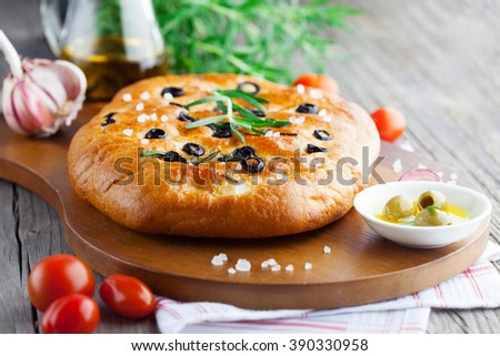 Freshly baked traditional Italian focaccia bread with rosemary and black olives on old wooden background, selective focus - stock photo