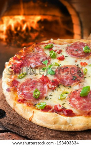 Freshly baked traditional Italian pepperoni or salami pizza on a crisp golden pie crust in front of a pizza oven fire in a restaurant or pizzeria - stock photo