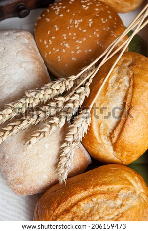 Freshly baked traditional rolls on cotton cloth with ears of wheat grain