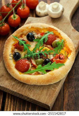 Freshly baked vegetarian mini pizza with arugula on wooden table