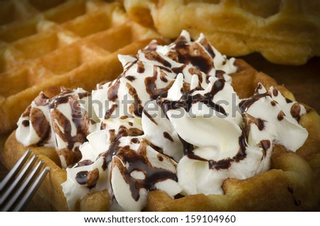 freshly baked waffles with milk cream close up on the wood