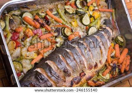 freshly baked wild salmon with vegetables in metal dish - stock photo