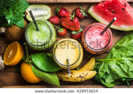 Freshly blended fruit smoothies of various colors and tastes in glass jars in rustic wooden tray. Yellow, red, green. Top view, selective focus - stock photo