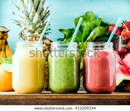 Freshly blended fruit smoothies of various colors and tastes  in glass jars. Yellow, red, green. Turquoise blue background - stock photo