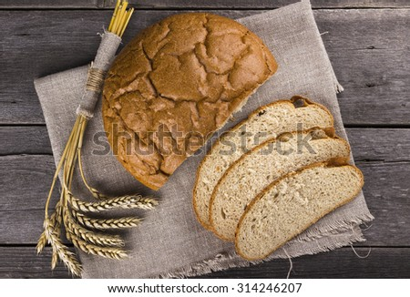 Freshly bread and ears of wheat on a wooden background. Top view