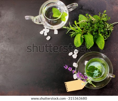 Freshly brewed peppermint tea with fresh herbal ingredients and flowers alongside in a glass cup and teapot for a refreshing healthy drink, overhead view on slate with copyspace - stock photo