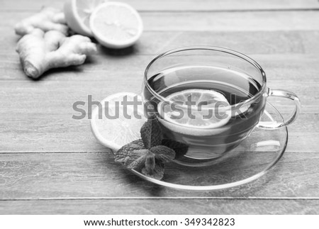freshly brewed tea in glass cup with lemon, mint and ginger on wooden background