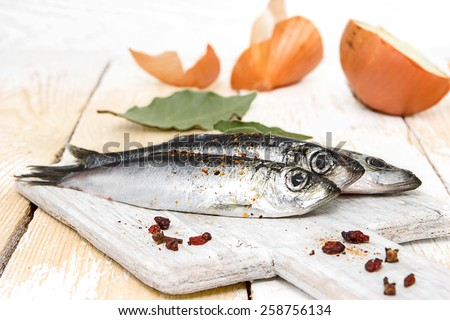 Freshly caught herring with spices on the wooden background - stock photo
