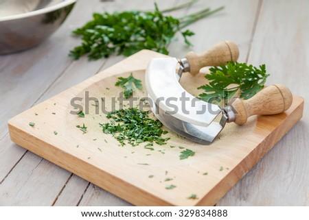Freshly chopped parsley on a board with mezzaluna  - stock photo