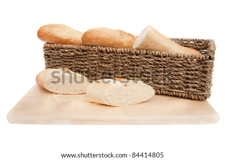 Freshly cooked baguette in rustic basket with bread knife on chopping board isolated on white