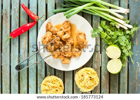Freshly cooked chicken pieces on a small plate with raw ingredients and dried noodles - stock photo