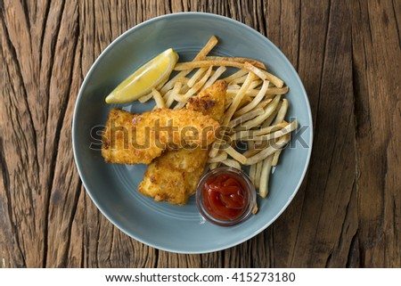 Freshly cooked fish and chips on a rustic wooden background. Gastropub style food. View from above. - stock photo