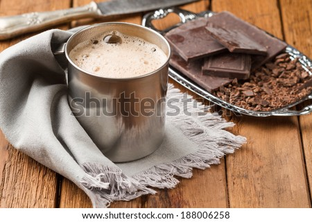 Freshly cooked hot chocolate with foam in a tin mug - stock photo