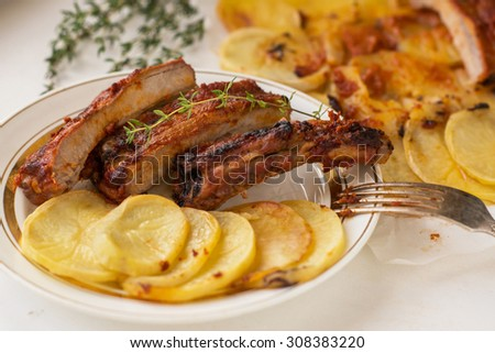 freshly cooked juicy pork ribs with potatoes on white background - stock photo