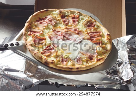 Freshly cooked  meat pizza with eggs pizza to delivery - stock photo