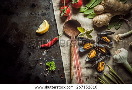 Freshly cooked mussels with savory ingredients for preparing a gourmet seafood appetizer including garlic, chili pepper, root ginger, tomatoes, coriander, bay leaf and spices with a rustic wood spoon - stock photo