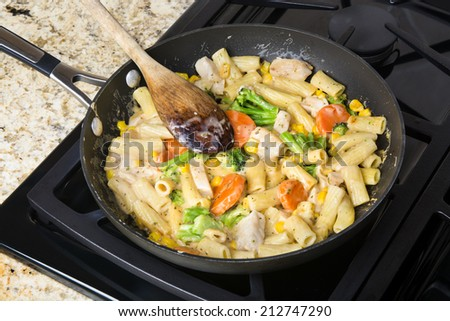 Freshly cooked pasta with vegetables, chicken and cream sauce in a stove top simmering pan - stock photo
