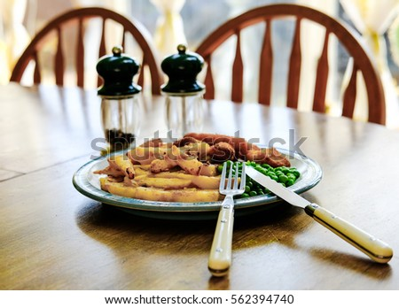 Freshly cooked plate of potato chips, fish fingers and peas seen on a kitchen table with condiments.