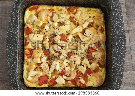 Freshly cooked prawn and sheep cheese omlette in a oven dish. - stock photo