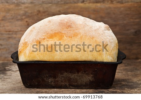 Freshly cooked white bread still in the bread pan - stock photo