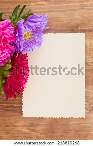 Freshly cut asters on wooden background and vintage card. Space for your text - stock photo