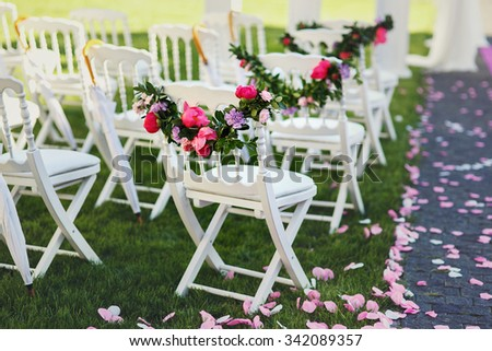 Freshly cut beautiful red and purple wedding flowers garland on chair